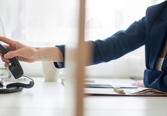 Gebäudereinigung München - Blick durch eine Bürotrennwand auf eine Geschäftsfrau oder Sekretärin, die einen Telefonhörer auswählt oder auflegt.